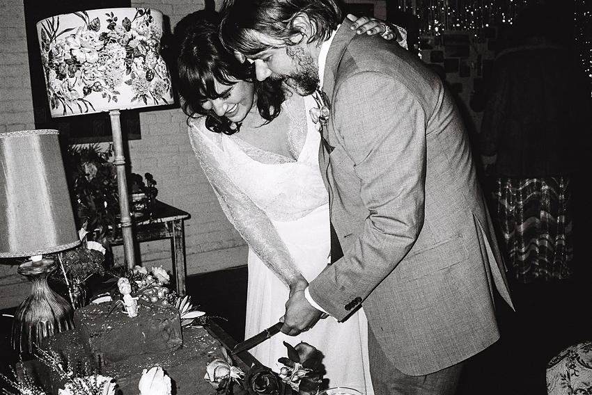 a photo of the wedding couple cutting the cake